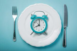A plate with a blue alarm clock with a fork on one side and a knife on the other side all on a blue background