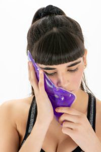 Woman with ice pack on her cheek