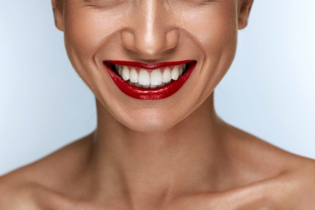Women smiling with white teeth and red lipstick