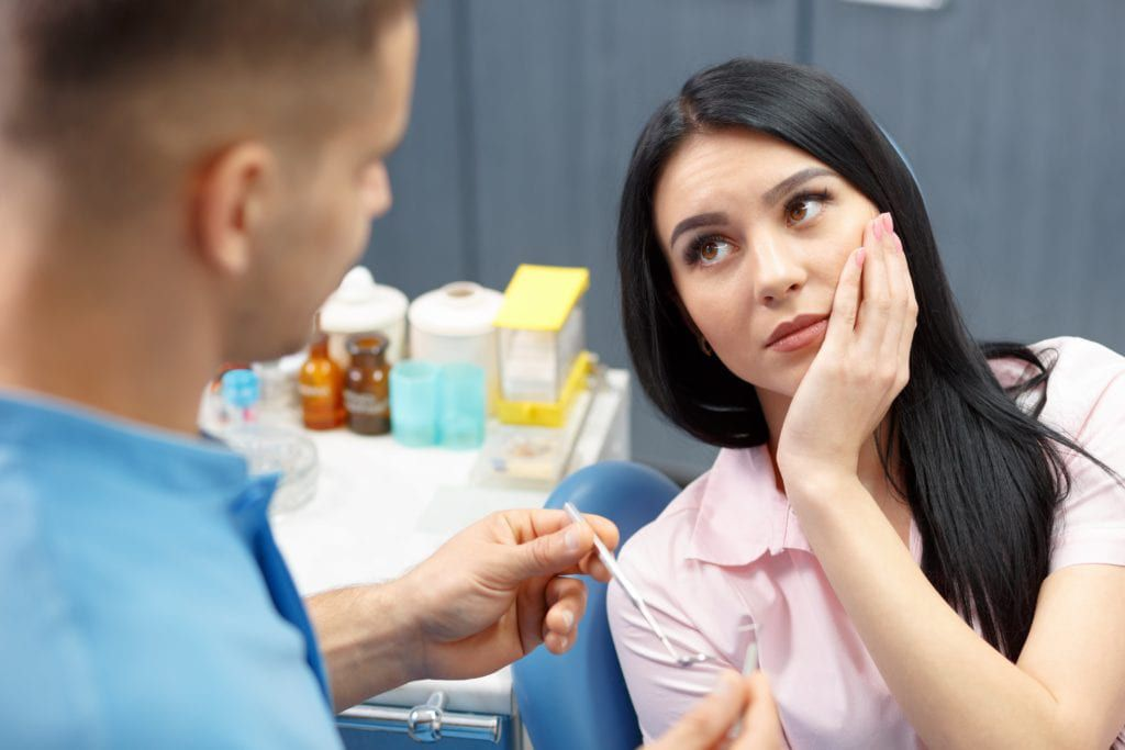 Woman with tooth pain sitting in a dental chair talking to dentist