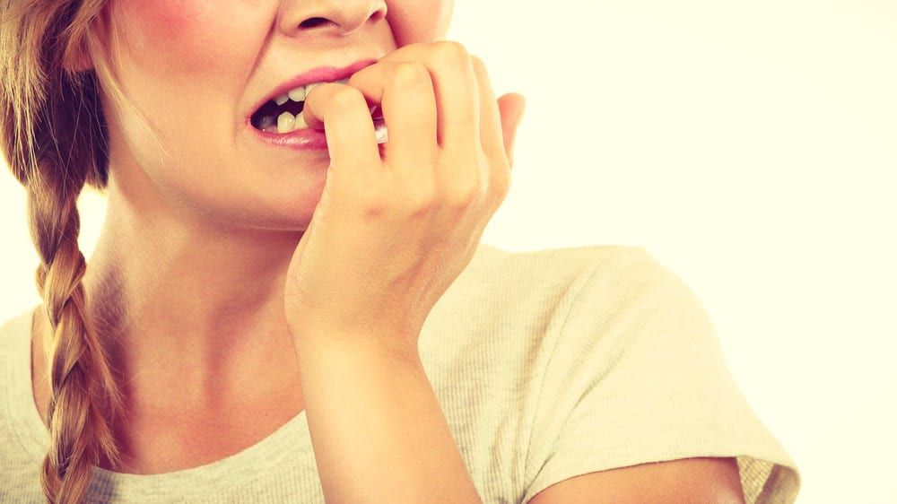 woman anxiously biting her nails