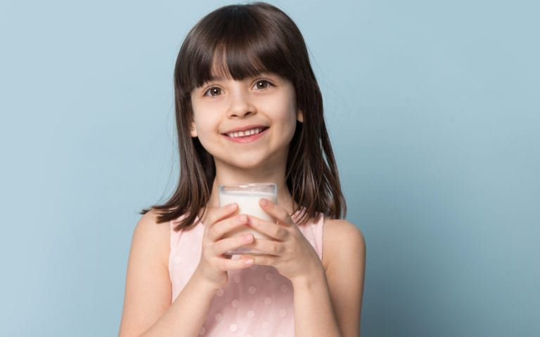 Smiling child with glass of milk